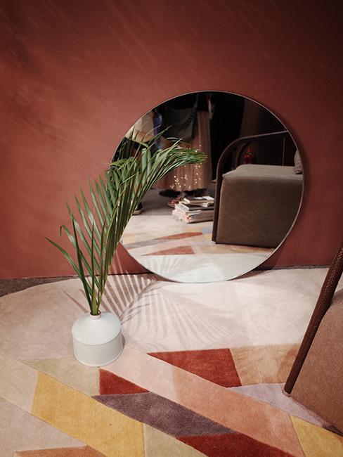 miroir rond posé au sol avec mur rose