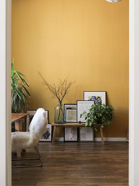 cadres sur banc en bois avec un mur jaune