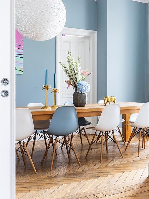 salle à manger avec grande table en bois et mur bleu