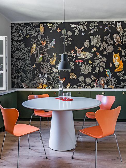 cuisine originale avec table ronde, chaises orange te papier peint végétal