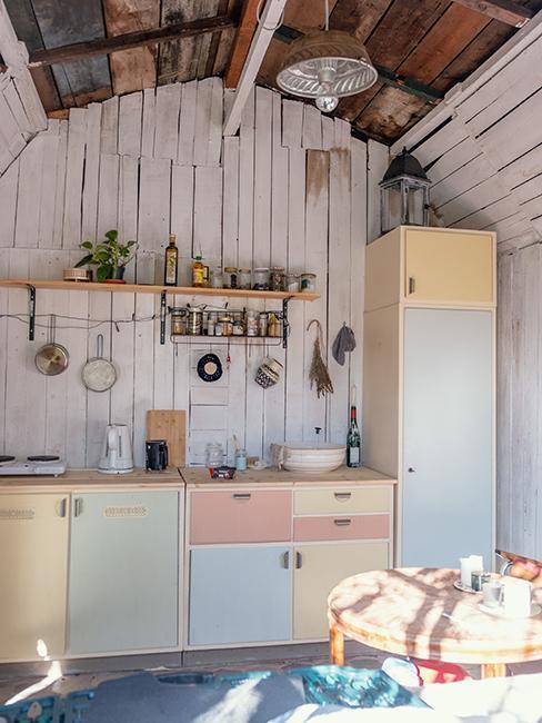 cuisine extérieur avec meubles pastel et mur en bois