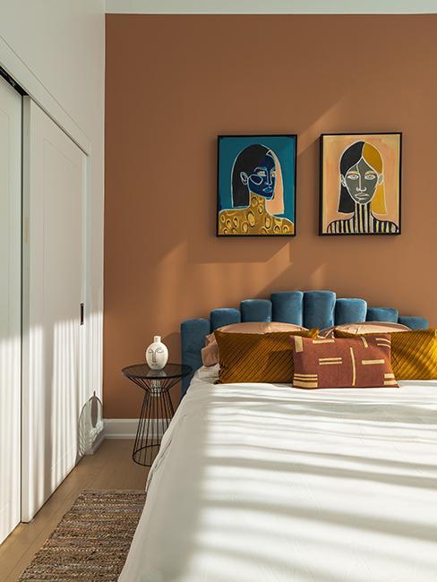 chambre avec mur couleur terre cuite et tete de lit en velour bleu