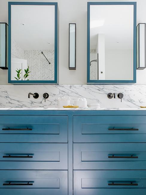 salle de bain avec mur effet marbre, meubles bleus et miroirs