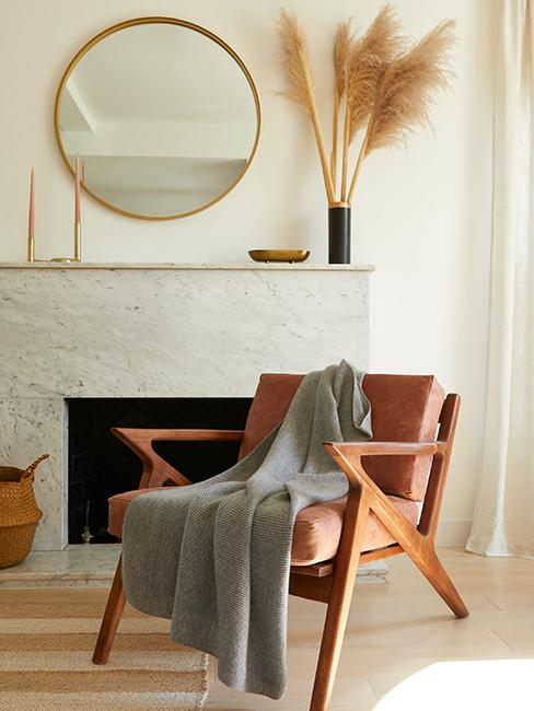 salon avec fauteuil et plaid gris, cheminée blanche et herbe de la pampa