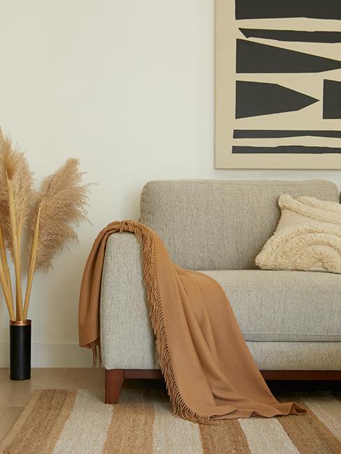 salon avec canapé gris, plaid et herbe de la pampa