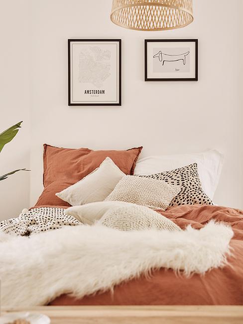 chambre avec linge de lit terracotta et mur de cadres