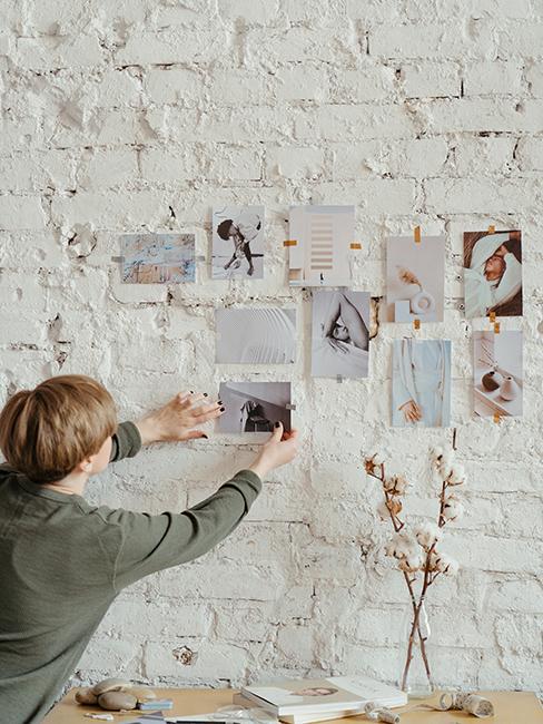 personne entrain d'accrocher des phot sur un mur en brique blanc