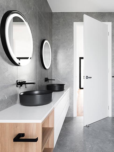 salle de bain moderne grise avec miroirs ronds et éclairage intérieur intégré au miroir