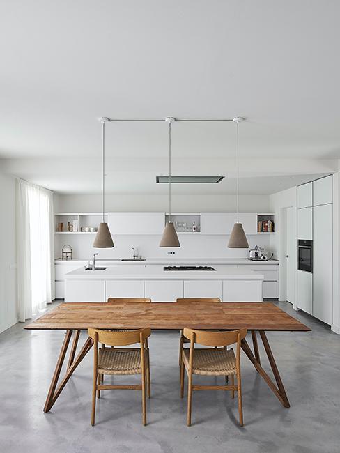 cuisine blanche avec grand table en bois et éclairage intérieur avec 3 suspensions taupe