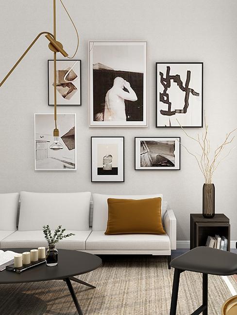 salon avec mur de cadres et canapé blanc