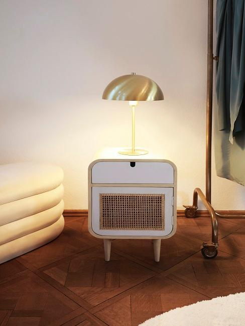 éclairage intérieur avec lampe dorée à poser sur un petit meuble en chevet blanc