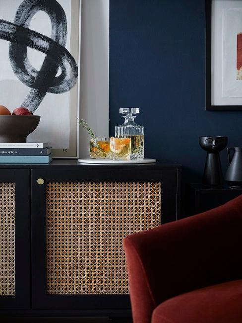 Commode en cannage, fauteuil rouge, mur bleu
