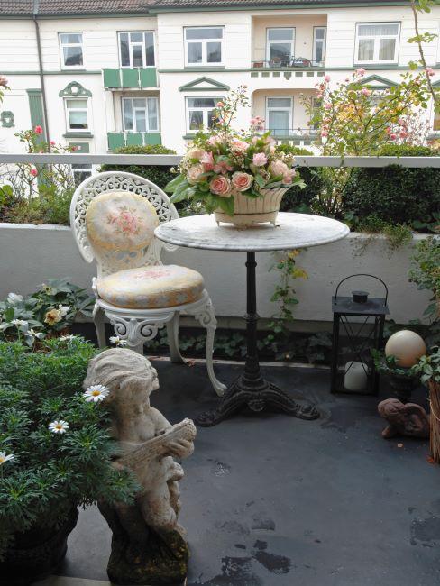 balcon à la française avec mobilier en fer forgé, bouquet de fleurs et lanternes