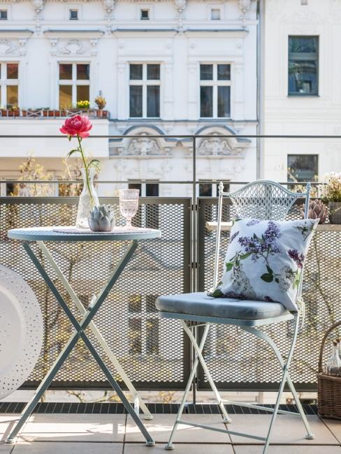petit balcon parisien avec meubles en fer forgé et coussin décoratif