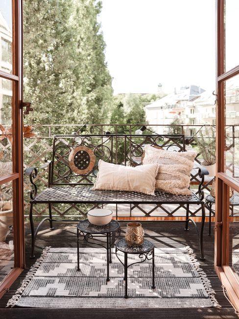 banc en fer forgé sur un petit balcon à la française avec coussins et tapis ethinque