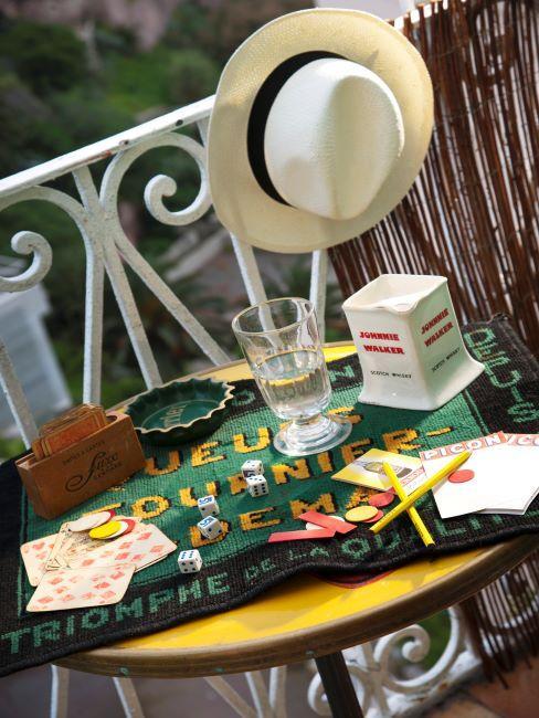 gros plan sur une petite terrasse, table en fer, jeux de cartes