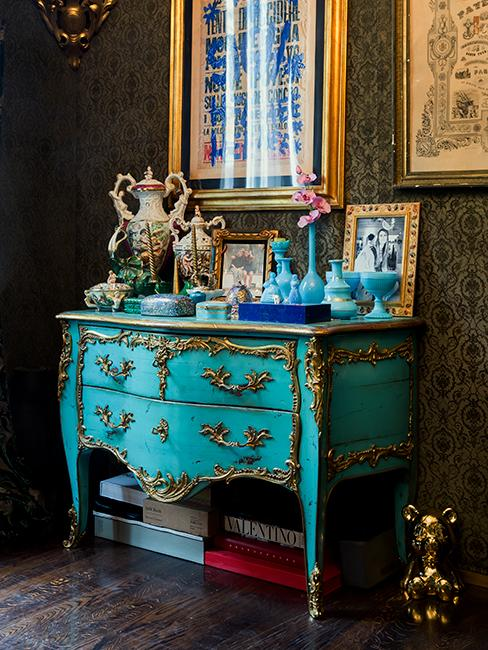 commode vintage bleue avec cadres dorés et objets décoratifs