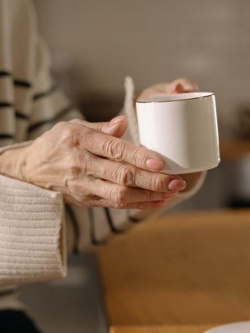 mains d'une personne agée avec une jolie tasse à café en porcelaine
