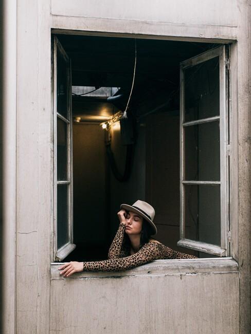 une femme avec un chapeau en train de profiter du moment présent à la fenêtre