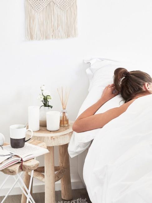 femme dans sa chambre a coucher, petite table de nuit en bois brut, bougies