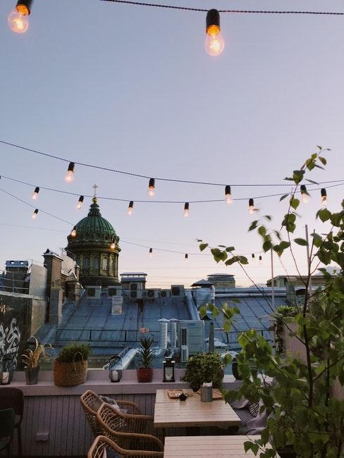 terrasse ouverte sur le toitavec mobilier ne bois et guirlande lumineuse
