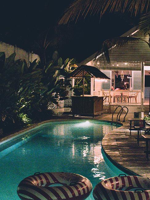 piscine avec bouées donut et bar dans la nuit