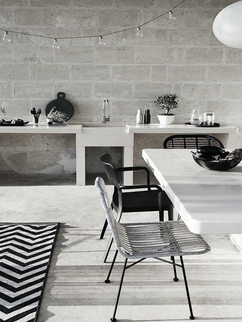 cuisine extérieur avec mur en brique, chaises ajourées, grande table