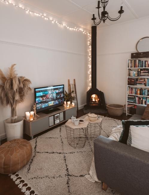 salon ethnique avec cheminée, guirlande lumineuse et meuble TV