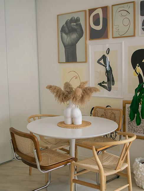 Salle à manger avec table ronde blanche et chaises dépareillées, mur de cadre chez mes yeux sur toi