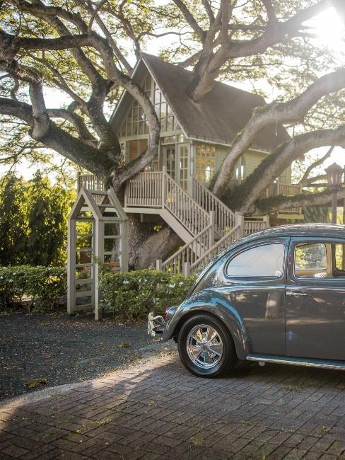 voiture vintage et cabane dans les arbres dans le jardin devant la maison