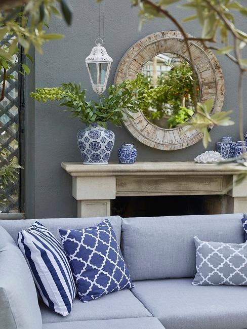 salon de jardin bleu avec coussin bleu, mur gris avec cheminée et miroir