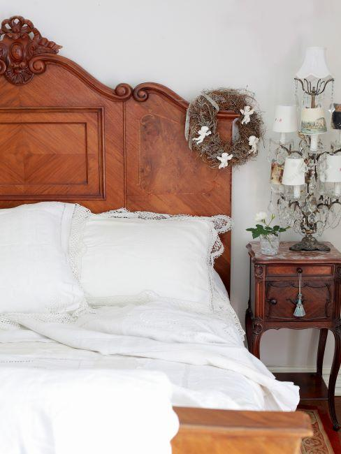 vieux lit en bois, tête de lit sculptée, petite table de chevet, lampe de nuit, linge de lit blanc