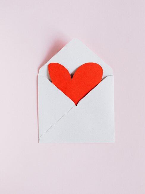 Enveloppe blanche ouverte avec coeur rouge sur fond rose