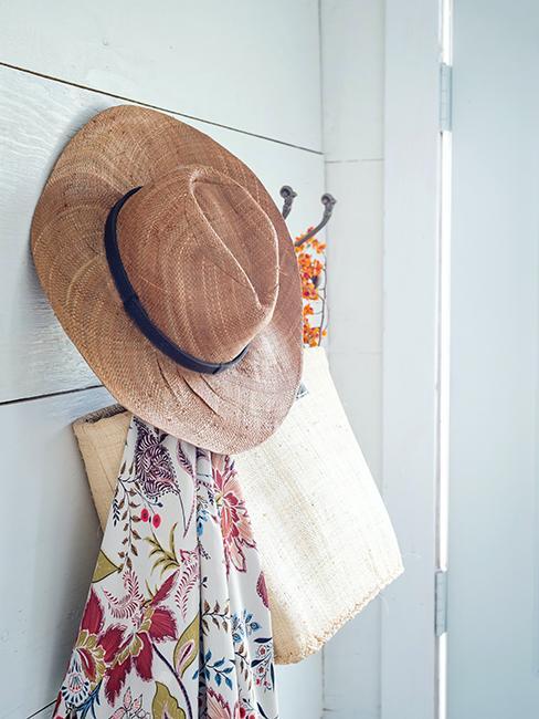 chapeau de paille accroché à un porte manteau