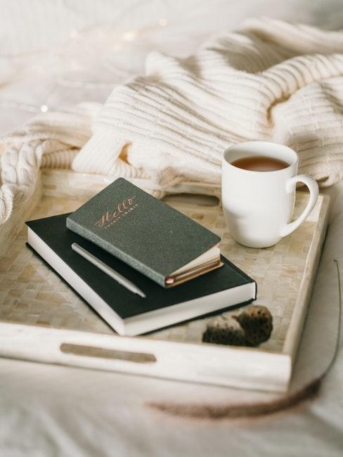 plateau crème avec cahiers, tasse à café et plaid