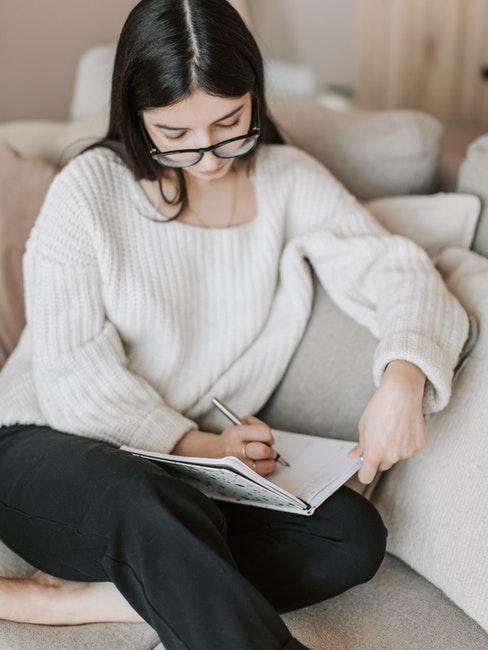 Femme assise sur le canapé dans le salon avec bullet journal