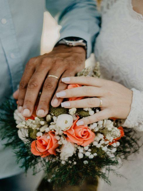 bouquet avec les mains de mariés, alliances de mariage
