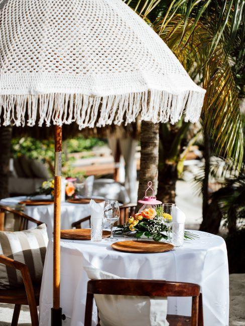 une petite table de mariage ronde, sous un parasol, mariage à l'étranger, mariage exotique