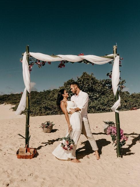 couple de mariés devant un petit autel romantique sur une plage exotique