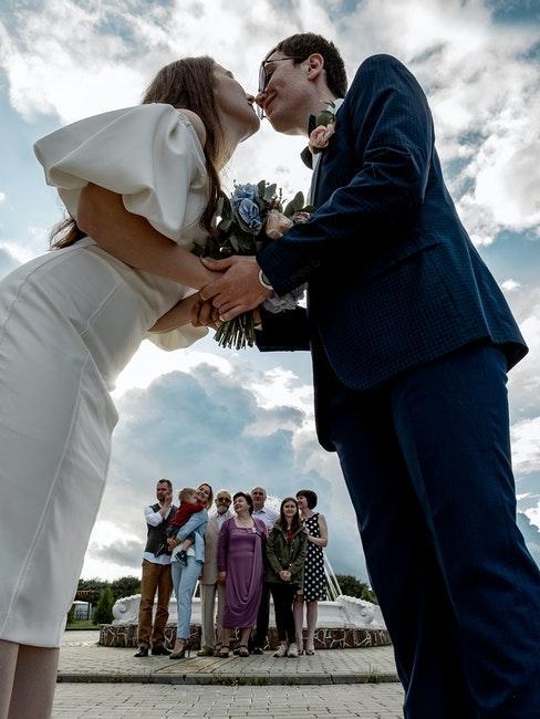 couple de mariés s'embrasse, invités applaudissent