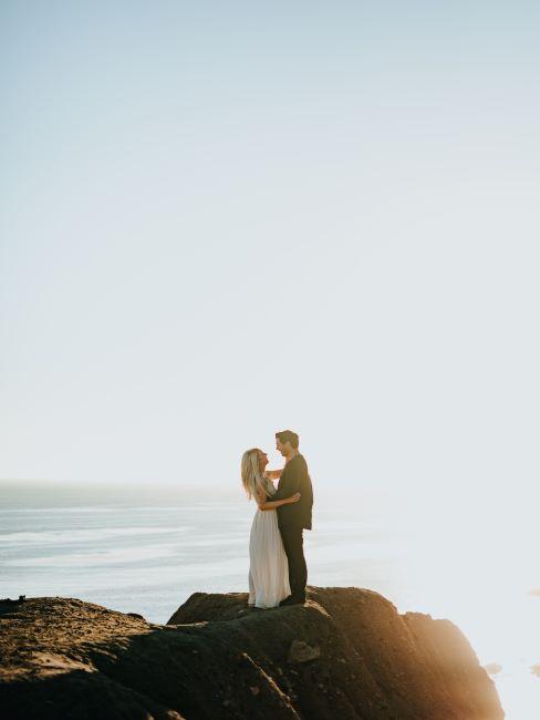 couple de mariés sur une roche avec l'océan dans le paysage