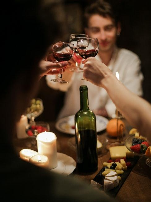 homme à table trinquant avec amis, vin rouge