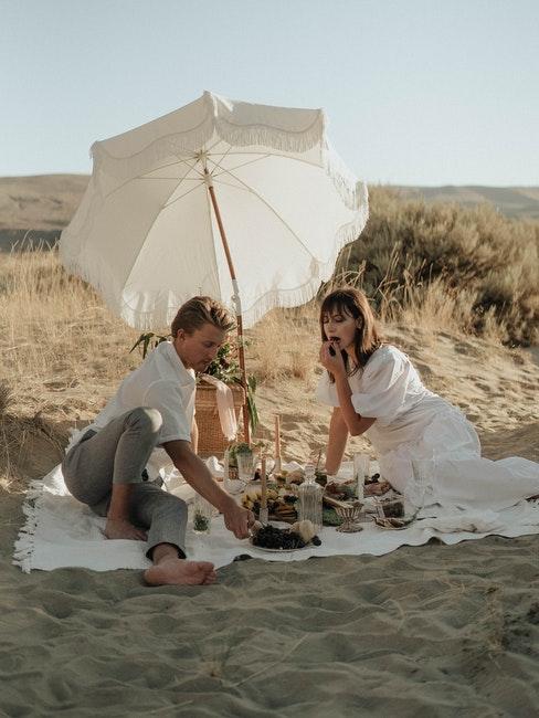 couple assis dans le sable, parasol blanc, plage, pique-nique en amoureux