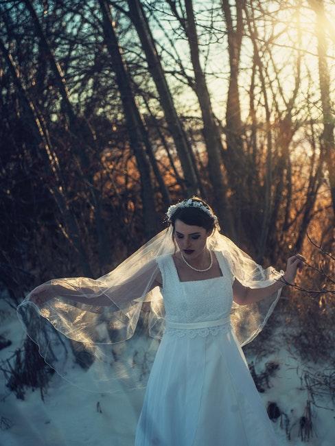 la mariée en robe blanche légère dans une forêt avec de la neige
