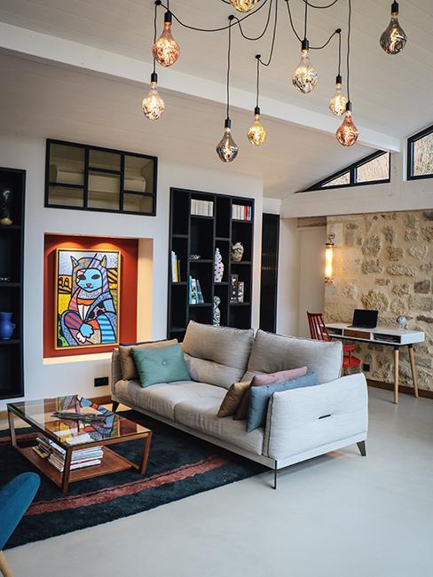Salon avec canapé gris, mur en brique, suspension avec des ampoules chez Julien Duquaire