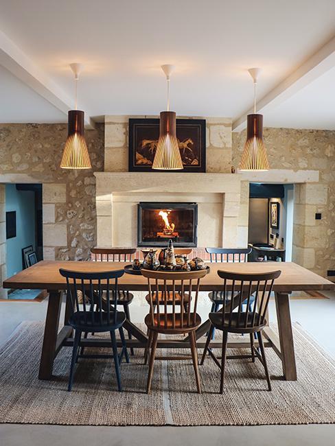 Salle à manger avec mur en brique et table en bois et cheminée dans la maison en pierre de Julien Duquaire