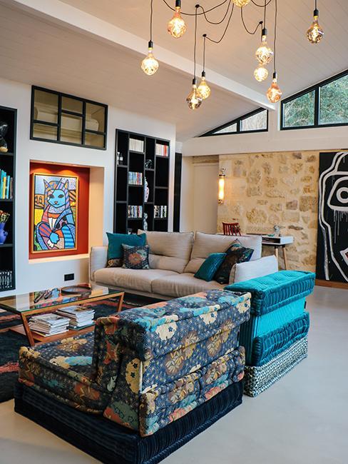 salon avec canapés lougne et mur en pierre dans la maison en pierre de Julien Duquaire