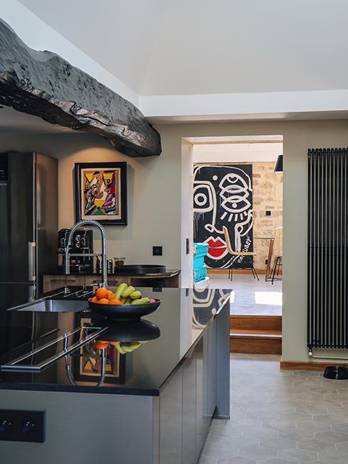 cuisine dans maison en pierre avec ilot de cuisine gris et poutre apparent chez Julien duquaire