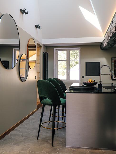 cuisine dans maison en pierre avec ilot de cuisine, chaises hautes en velours vertes et miroirs ronds chez Julien duquaire