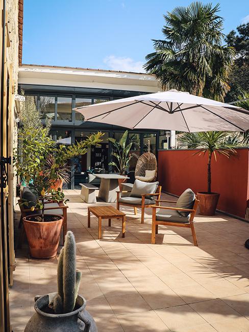 terrasse avec set de jardin en bois et grand parasol blanc chez Julien Duquaire